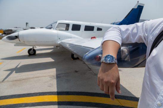Brazo de un hombre con el reloj Autavia recargado sobre el ala de un avión blanco con azul