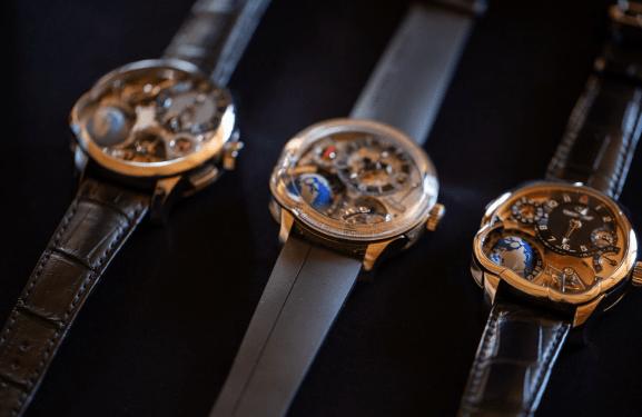 Relojes con correas negras y caratula en color dorado con la figura de un mundo en la parte inferior