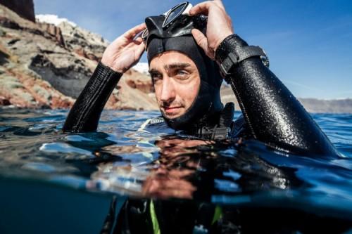 Hombre con traje de buzo y googles dentro del mar