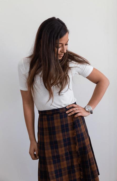 Estudiante de Diseño de relojes Iris Gigon con blusa blanca y falda de cuadros