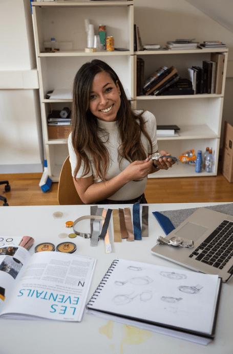 Iris Gigon sentada frente a una mesa con herramientas de relojería mostrando su reloj