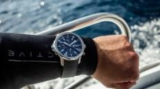 Brazo de un hombre con traje de buzo usando un reloj con correas negras y caratula plateada de IWC Cousteau Divers