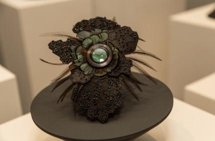 Reloj en tono café con detalles en verde y pqueñas plumas