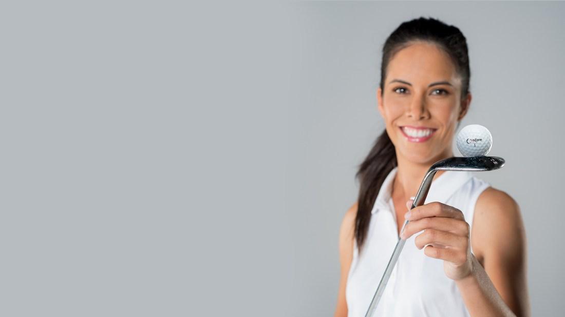 Tania Tare sonriendo con blusa blanca y un palo de golf en las manos