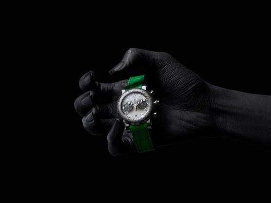 Mano sosteniendo el reloj Joker con correas verdes