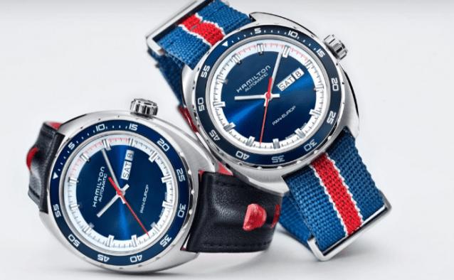 Reloj con correas negras y caratula plateada junto a reloj con correas en color azul con rojo y caratula plateada