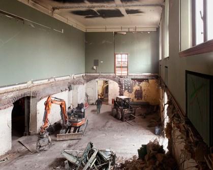 In deze ruimte – die vroeger dienst deed als auditorium – is de vloer uitgebroken. In het nieuwe museumgebouw zal op deze plek de museumshop komen.