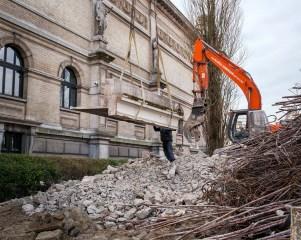 Eenmaal uit het gebouw kan een graafkraan met betoncrusher het betonstuk verbrijzelen.