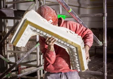 Eenmaal genummerd draagt een arbeider de stukken sierlijst naar een plek waar ze veilig opgeborgen worden. Foto: Karin Borghouts
