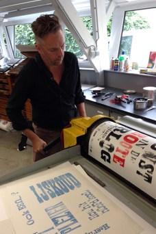 Bob drukt. Een zware cilinder trekt het papier met kracht over de houten letters. Zo ontstaat de afdruk. De beïnkte letters geven hun spiegelbeeld af.
