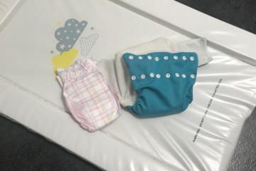 A reusable modern cloth nappy and a disposable nappy on a change mat
