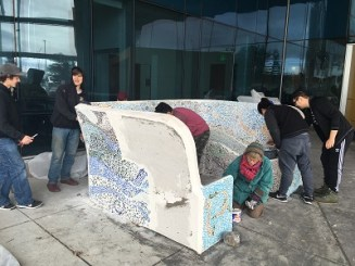 Students and helpers work on mosaic bench at Kodiak High School. Kayla Desroches/KMXT