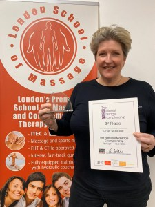 Picture of Una Tucker holding a trophy and certificate in front of a London School of Massage banner