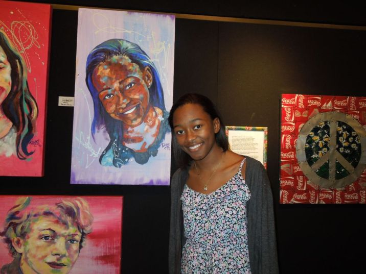 Sophomore Morgan Brewton-Johnson poses next to a painting of herself
