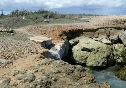 Een pijp vlakbij Playa Kanoa waar afvalwater de zee in wordt geloosd