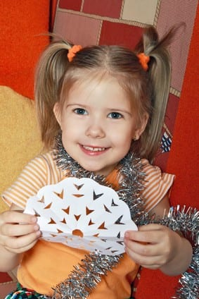 Little girl holding up paper snowflake and smiling