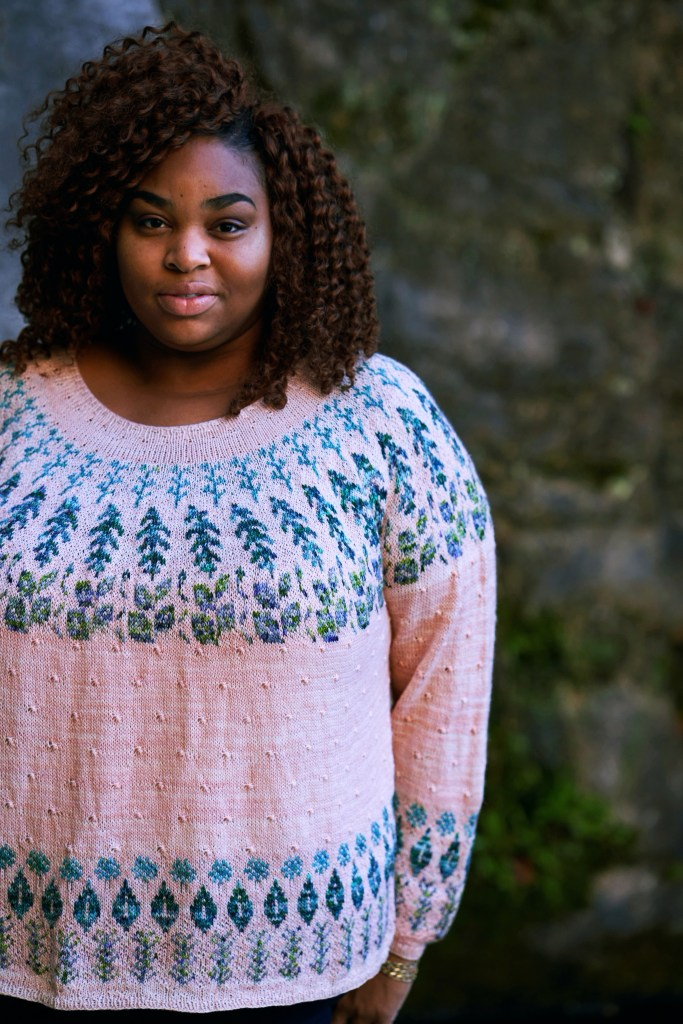 A large black woman faces the camera. She is wearing a soft pink handknit sweater featuring various teal and green herbal motifs at the yoke, hem and cuff.