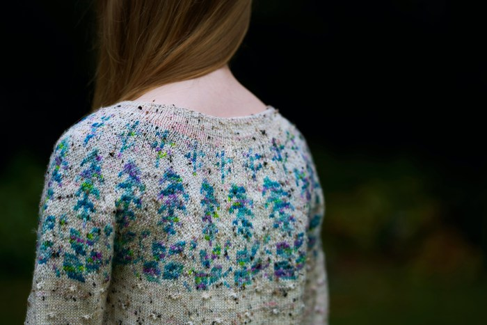 The upper back of a handknit sweater is shown on a little girl. THe sweater is warm gray with teal and purple herbal motifs around the yoke.