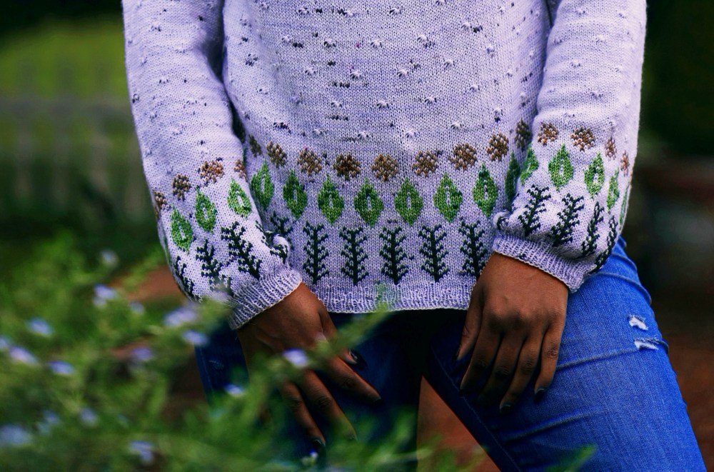 A closeup of the bottom of a sweater that is lavender-colored with brown dandelion puffs, green basil leaves and dark green rosemary sprigs arranged along the hem and cuffs