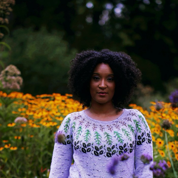 A black woman stands in front of a large cluster of yellow coreopsis flowers.
