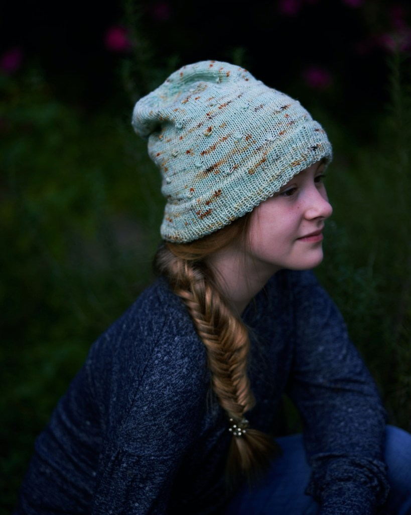 A young girl with a fishtail braid to the side is wearing a minty green slouchy hat with golden speckles.