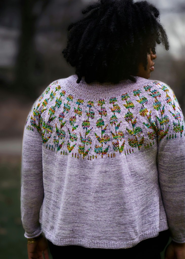 Back view of a gray handknit sweater with rainbow milkweed motifs in the yoke