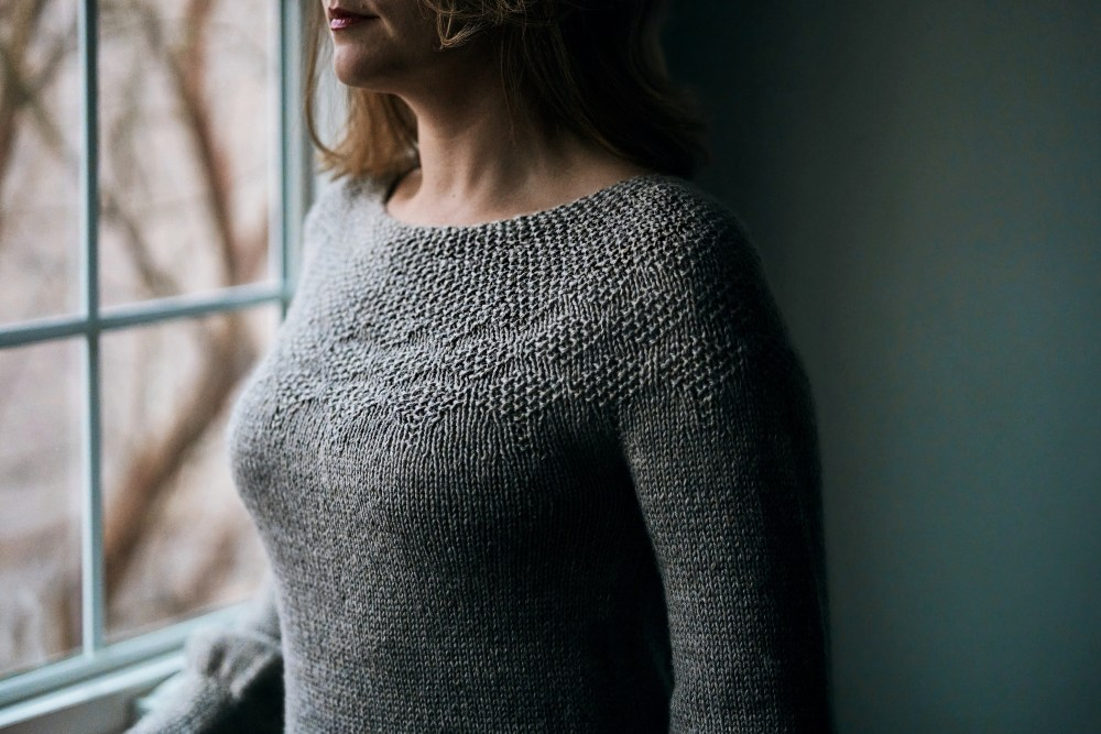 Closeup of a gray hand knit sweater with a seed stitch yoke