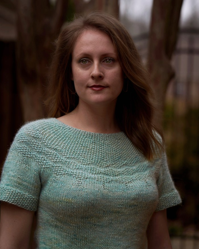 Portrait of Jamie wearing a minty green short sleeved hand knit sweater with seed stitch at the yoke.
