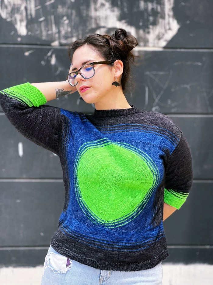 A woman holds her hand above her head and is modeling a dark gray, royal blue and neon green handknit sweater