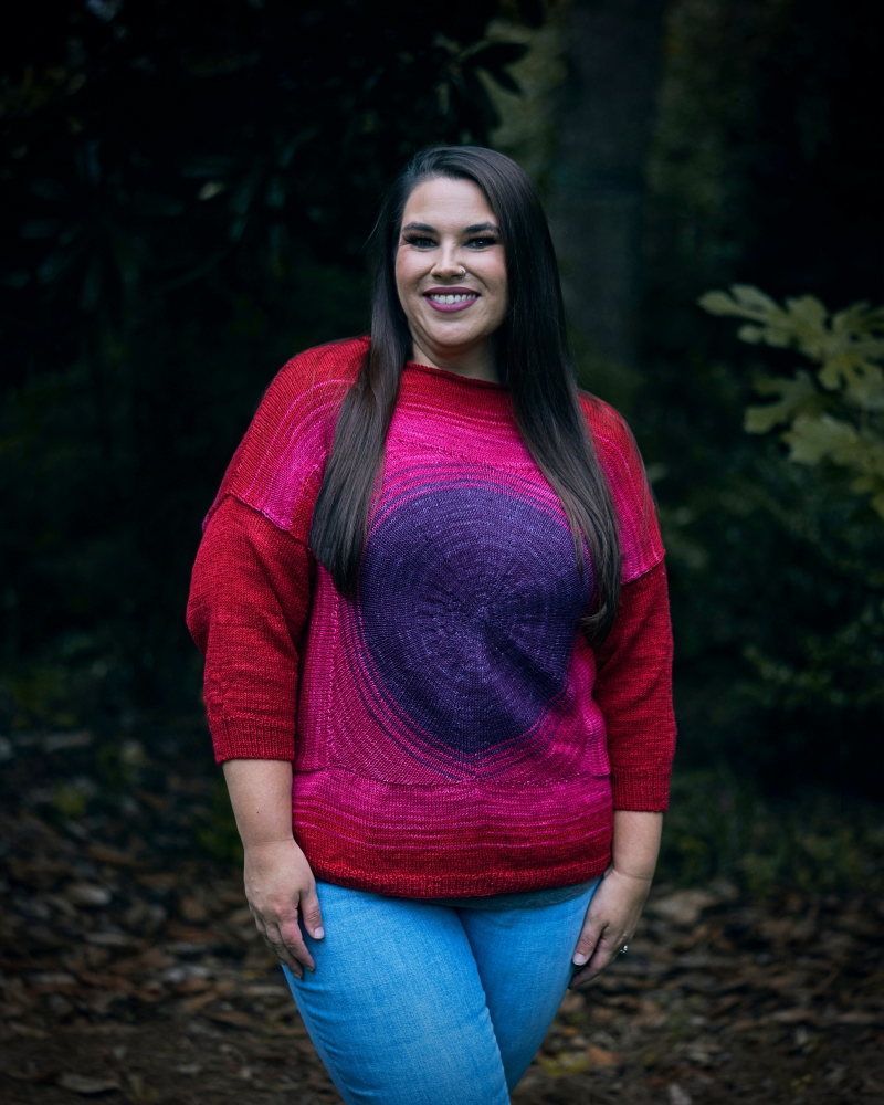 A woman gazes at the camera. She is modeling a red, pink and purple three-quarter sleeve handknit sweater