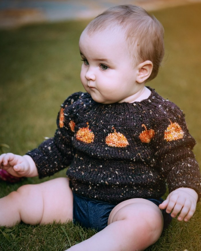 A one year old baby wears a handknit sweater that is brown with orange pumpkins in the yoke