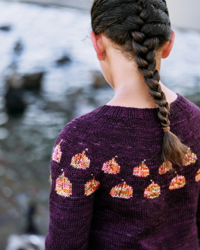 A 9 year old girl wears a purple handknit pullover with orange and pink pumpkins in the yoke