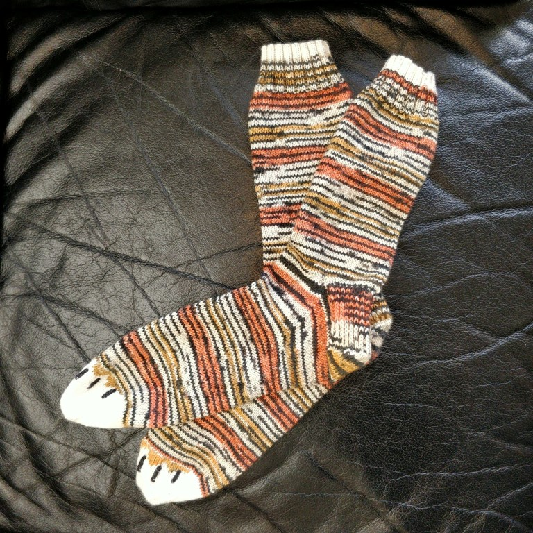 A pair of tiger-striped socks with white toes and embroidered claws, laid smoothly on a black leather couch