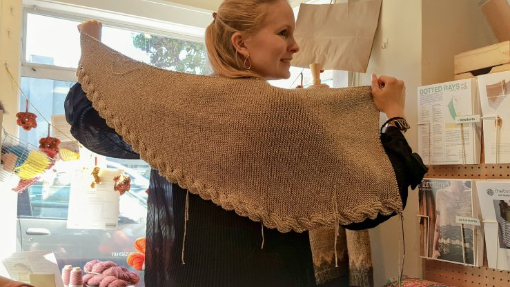 Knitted shawl being held up across shoulders