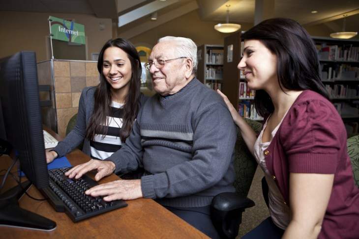 Older man using computer in library with two women