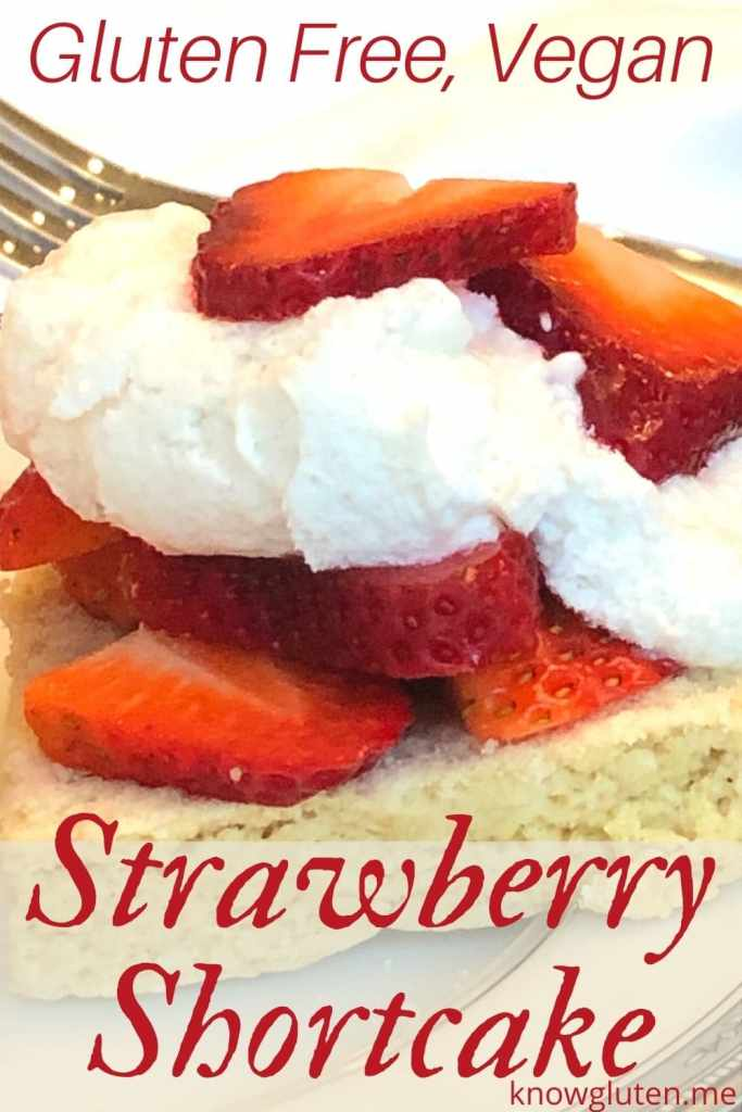Closeup of gluten free strawberry shortcake on a plate with a fork in the background.
