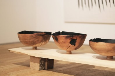three large turned vessels on a bench in exhibition