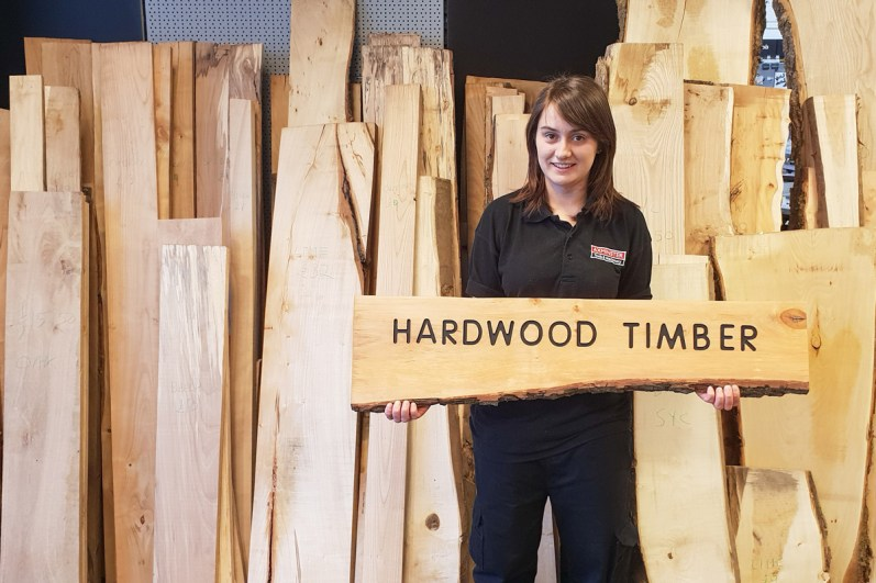Lydia in front of our beautiful selection of hardwood