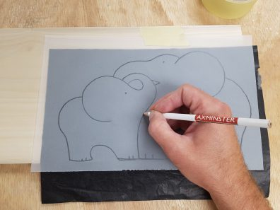 Using carbon paper to transfer the design