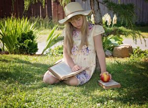 Young girl reading a book outside