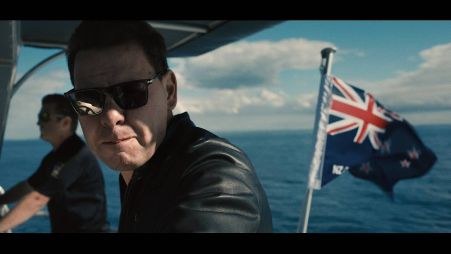 Still from the On P documentary showing Patrick Gower in sunglasses and slick black shirt on a boat with the New Zealand flag in the background
