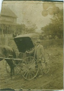 Black and white image of man with horse and carriage