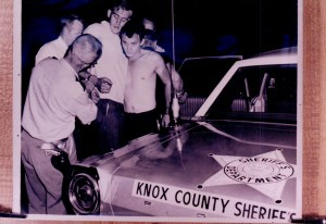 Black and white image of officers arresting two men next to cruiser