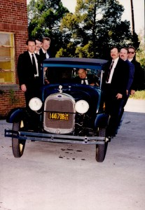 Officers in suits standing and sitting in old 1940's car