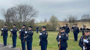 Honor Guard Standing at attention with rifles as Bagpiper plays