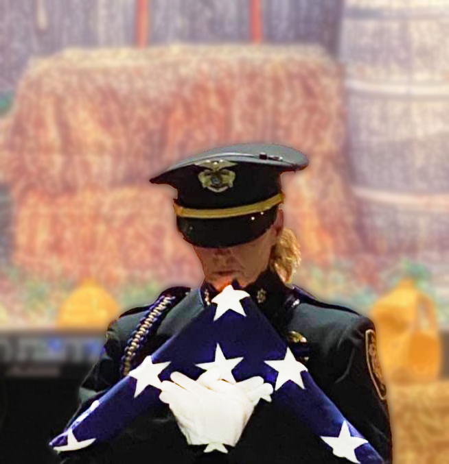 Female Honor Guard officer holding triangle folded American flag