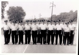 Black and white image of officers standing in road looking at camera