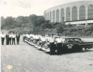 Black and white photo of officers standing next to their cruisers