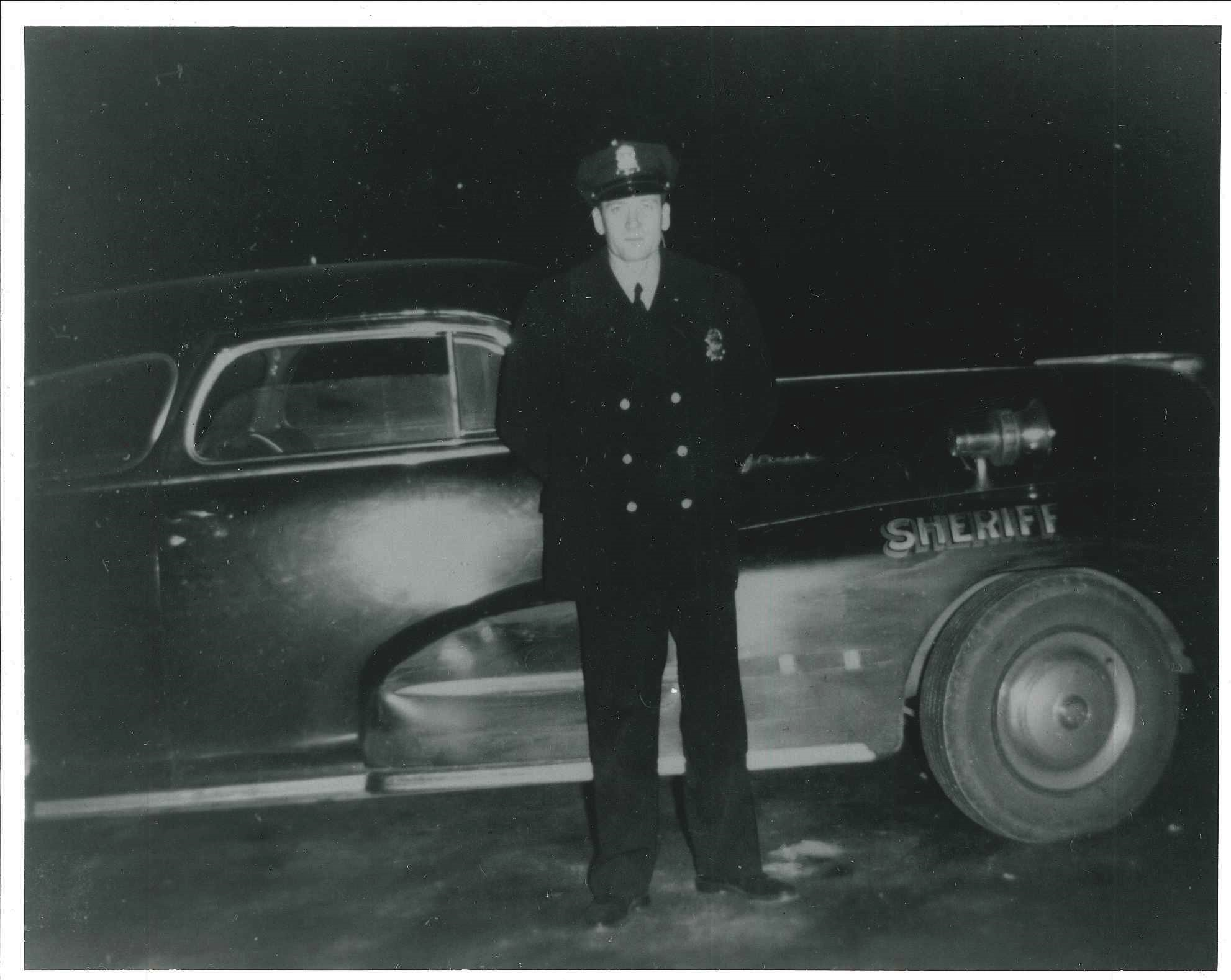Old black and white photo of officer standing next to cruiser
