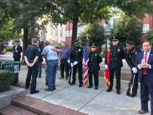 Honor guard at attention and hugging civilian with Sheriff and Chief Deputy